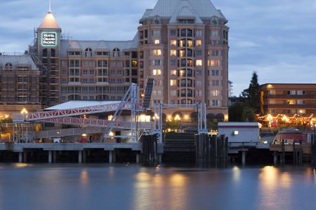 victoria bc: VICTORIA, BC, CANADA - MAY 17 2016: Night view of the Inner Harbor Downtown. Tourists strolling the causeway. This waterfront is the location of many tourist attractions and recreational activities. Editorial