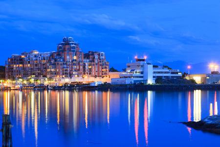 actividades recreativas: Victoria, BC, Canadá - 17 MAY 2016: Vista nocturna del puerto interior del centro. Los turistas dan un paseo de la calzada. Este muelle es la ubicación de muchas atracciones turísticas y actividades recreativas.