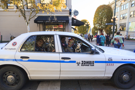 VICTORIA CANADA OCT 29 2016: Zombies takes over Victoria. Young people in costumes participating. Zombie Walk is an annual event, Zombie Patrol dressed as a soldier, guard the civilians from zombies.