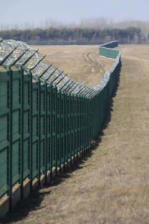 Fence with barbed wire on top used for borders protection.