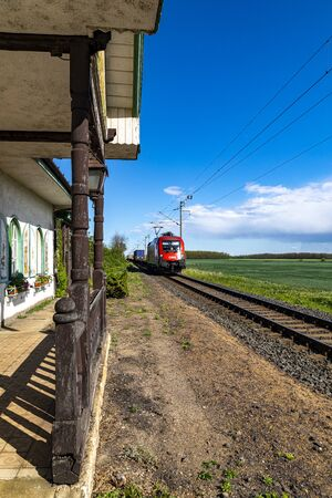 Hungary Debrecen May 2, 2020: A red colored electric locomotive pulls a freight train in the countryside.