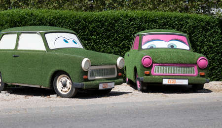 Sopron Hungary May 2, 2020: Two east german car - the famous TRABANT - fully decorated with artificial turf are on display by the Hwy. Him & Her Editoriali
