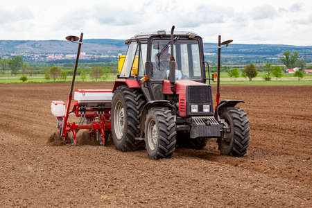 Debrecen Hungary - May 2020: Modern tractor towing a seed planting machine on a ploughed field in a rural area in Hungary in Springtime. Editorial