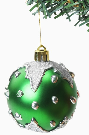 Green bauble hanging on a Christmas tree photo