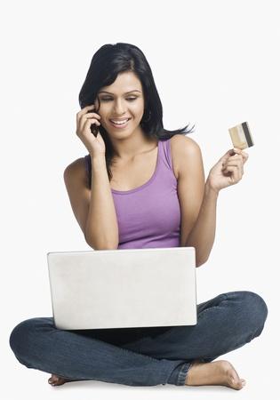orden de compra: Mujer de compras en l�nea y hablando por un tel�fono m�vil