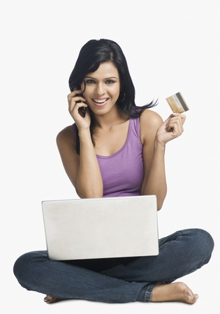 Woman shopping online and talking on a mobile phone Imagens