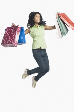retail therapy: Woman carrying shopping bags and jumping