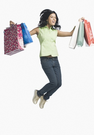 Woman carrying shopping bags and jumping