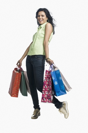 retail therapy: Woman carrying shopping bags and smiling