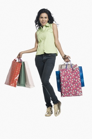 carrying: Woman carrying shopping bags and smiling