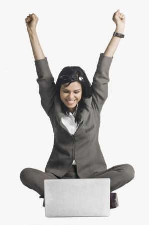 Donna sorridente con le braccia sollevate davanti a un computer portatile Archivio Fotografico - 10123440
