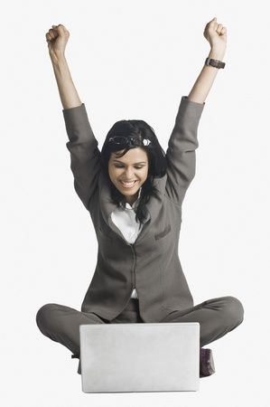 Woman smiling with her arms raised in front of a laptop