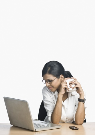 working: Businesswoman working on a laptop and drinking coffee