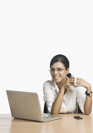 telecommunicating: Businesswoman working on a laptop and drinking coffee