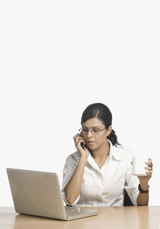 full height: Businesswoman talking on a mobile phone in front of a laptop