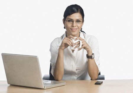 Businesswoman in front of a laptop and drinking coffee