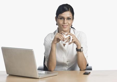 Imprenditrice davanti a un computer portatile e bere il caff� Archivio Fotografico - 10123438