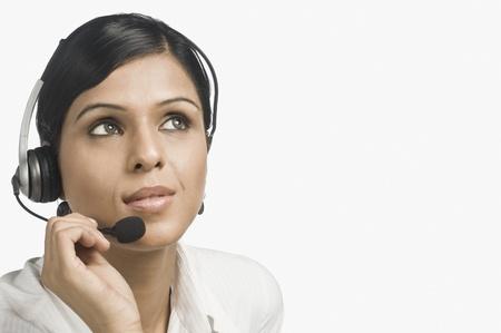 customer service representative: Close-up of a female customer service representative thinking
