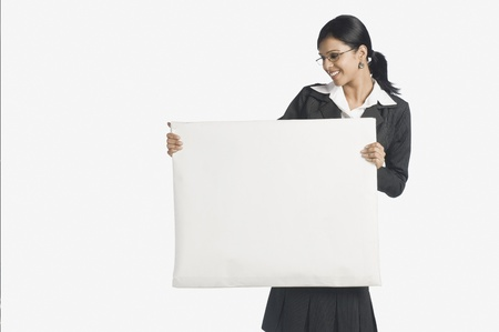Businesswoman holding a blank placard and smiling