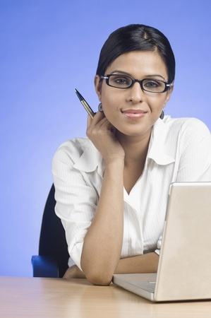 full height: Businesswoman working on a laptop and smiling