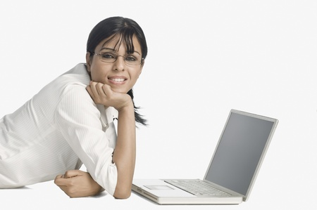 Woman lying in front of a laptop and smiling Foto de archivo
