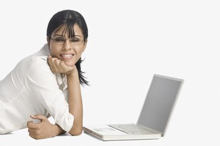 Mujer mentir delante de un ordenador port�til y sonriente Foto de archivo - 10123432