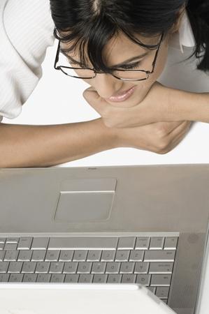 La mujer se encuentra frente a una computadora portátil y sonriente Foto de archivo - 10169554