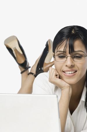 net surfing: Donna utilizzando un computer portatile e sorridente LANG_EVOIMAGES