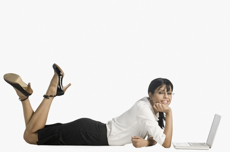 Woman lying in front of a laptop and smiling Archivio Fotografico