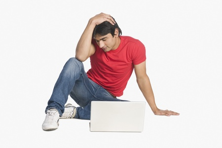 tense: Man sitting in front of a laptop