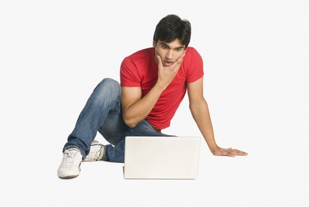 Man looking at a laptop with shocked expressions Stock Photo