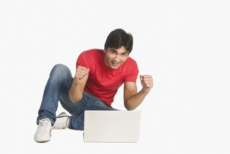 Man sitting in front of a laptop and smiling