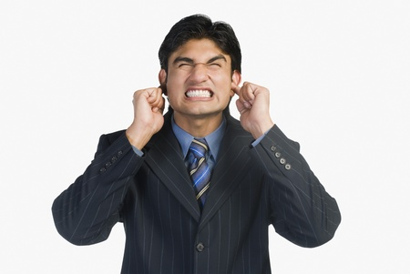 noisy: Businessman with his fingers in ears