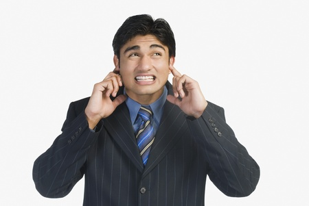 Businessman with his fingers in ears Stock Photo - 10123452