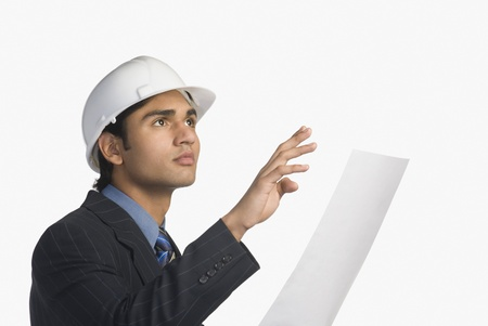 architect drawing: Architect holding a blueprint LANG_EVOIMAGES