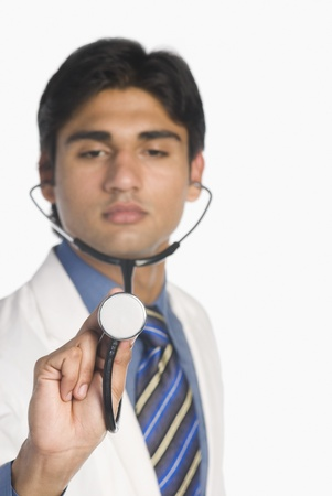 stethoscope: Doctor holding a stethoscope LANG_EVOIMAGES