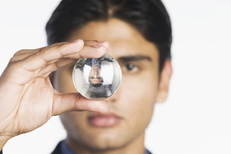 crystal background: Businessman holding a crystal ball LANG_EVOIMAGES