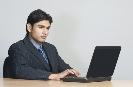 working at office: Businessman working on a laptop