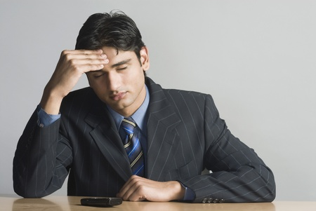 Businessman rubbing his forehead Banque d'images