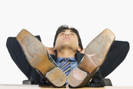hands behind head: Businessman with feet up on a desk LANG_EVOIMAGES