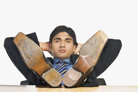 head rest: Businessman with feet up on a desk LANG_EVOIMAGES