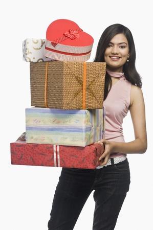 Femme détenant des coffrets cadeaux et souriant Banque d'images - 10169543