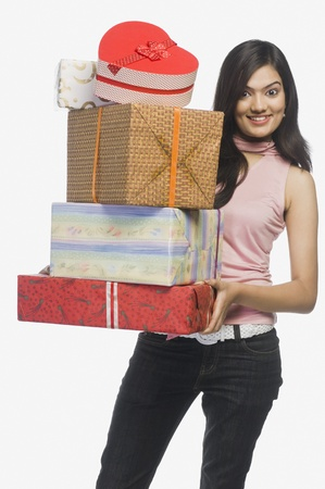 full height: Woman holding gift boxes and smiling