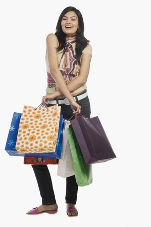 Woman carrying shopping bags and smiling Stock Photo - 10123398