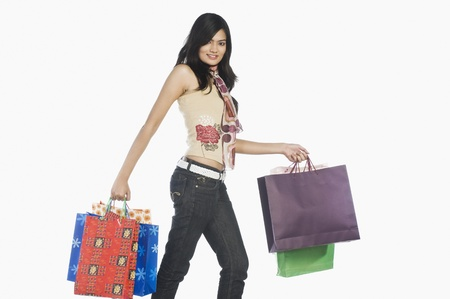 Woman carrying shopping bags and smiling Stock Photo - 10126413