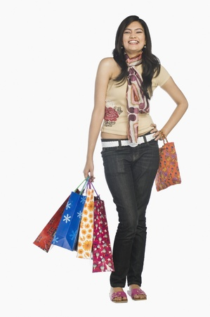 full height: Woman carrying shopping bags and smiling