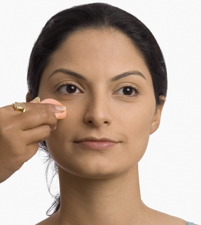 photosindia: Persons hand applying powder puff on a young womans face