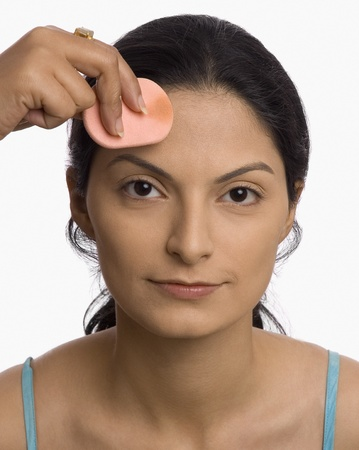 Persons hand applying powder puff on a young womans face