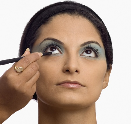 photosindia: Persons hand applying eye liner on a young woman LANG_EVOIMAGES