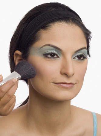photosindia: Persons hand applying make-up brush on a young womans face